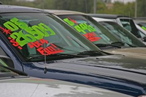 A display of cars for sale with prices in front
